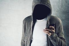 Anonieme persoon die met een kap mobiele telefoon, identiteitsdiefstal met behulp van concep Stock Foto