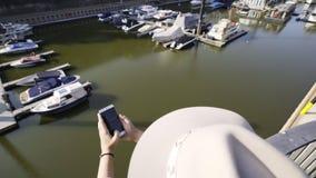 Anonieme vrouw die smartphone op dijk gebruikt stock footage
