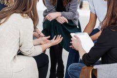 Anonieme vrouwen die in cirkel tijdens groepsvergadering zitten stock foto's