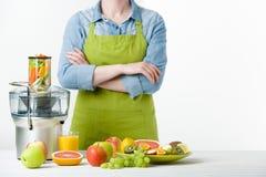 Anonimowa kobieta jest ubranym fartucha, przygotowywa świeżego owocowego sok używać nowożytnego elektrycznego juicer, zdrowy styl fotografia royalty free