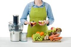 Anonimowa kobieta jest ubranym fartucha, przygotowywa świeżego owocowego sok używać nowożytnego elektrycznego juicer, zdrowy styl fotografia stock