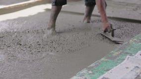 Anonimowy Betonowy Robotnik Wygładzający Chodnik Na Mokradłach. nalewanie betonu zbiory