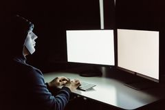 Anonimowy i zamaskowany hacker używa komputer z odosobnionym białym monitoru ekranem wkładać jakaś tekst, słowo, obrazki obraz royalty free