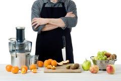 Anonimowy mężczyzna jest ubranym fartucha, przygotowywający świeżo robić owocowego sok, używać nowożytnego elektrycznego juicer,  zdjęcie stock
