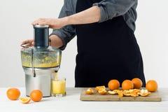 Anonimowy mężczyzna jest ubranym fartucha, przygotowywający zdrowego sok pomarańczowego, używać nowożytnego elektrycznego juicer, zdjęcia stock