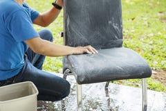 Anonimowy męski pracownik czyści krzesła zdjęcia royalty free