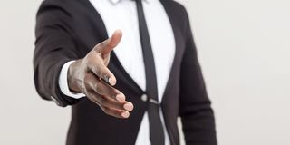 Anonym afro man showing hand at camera and need handshake. Man hand in black suit and tie giving hand to greeting or handshake at camera. focus on hand. indoor royalty free stock photos