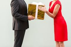 Anonym businessman give a present woman in red dress. Anonym businessman give a present women in red dress. Studio shot on gray background royalty free stock image