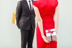 Anonym couple standing each other and holding gift box behind sp. Ine. Studio shot, gray background stock photo