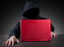 Anonym with hood and red laptop. Anonym hacker with hood and red laptop royalty free stock photos
