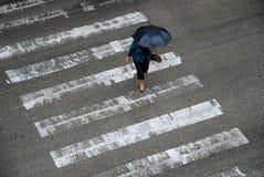 Anonym kvinna med paraplycrossinggatan royaltyfri fotografi