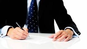 Anonym man i dräkt som undertecknar ett avtal Arkivfoton