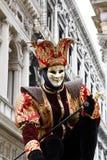 Anonym man som maskeras som en domstolgyckelmakare för den Venedig karnevalet Historisk byggnad på bakgrunden arkivfoton