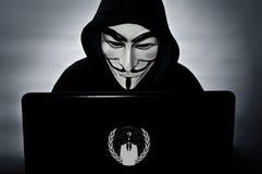 Anonym medlem med datoren med fejdmaskeringen Arkivfoton