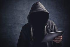 Anonym oigenkännlig man med den digitala minnestavladatoren