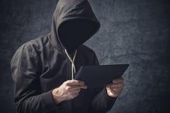 Anonym oigenkännlig man med den digitala minnestavladatoren Arkivbilder