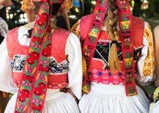 Anonyma flickor i folkloredräkter arkivfoton