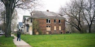Anonyma Person Walks Sidewalk Derelict Abandoned inhyser Detroit arkivfoton