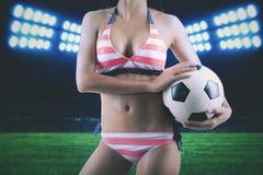 Anonyme Frau mit Fußball am Fußballplatz lizenzfreies stockbild