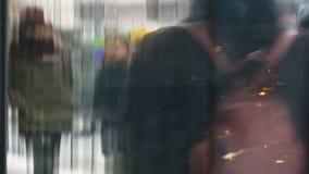 Anonyme Leute, die in die Straße einer Stadt mit Schaukastenreflexionen gehen stock footage