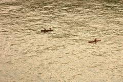 Anonyme Leute, die ein Boot rudern lizenzfreie stockfotografie