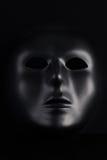 Anonyme schwarze Maske, die vom pechschwarzen Hintergrund hervorsteht Lizenzfreies Stockbild