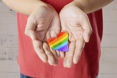 Anonymer Mann, der Herz mit Regenbogenfarbe hält Lizenzfreie Stockfotos