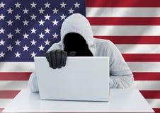 Anonymer Verbrecher in der Haube mit Laptop vor amerikanischer Flagge Lizenzfreie Stockfotos