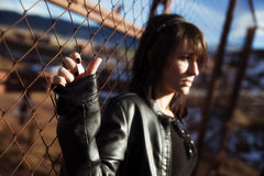 Anonymes Frauenporträt über Zaun Stockfotografie