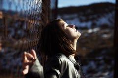Anonymes Frauenporträt über Zaun Lizenzfreies Stockfoto