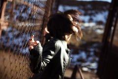 Anonymes Frauenporträt über Zaun Stockbild