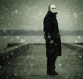 Man with white mask. Anonymity concept ,man near the river and snow f/x Stock Photo
