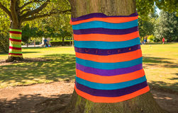 Anonymous art to give color to our grey cities. Two trees in a park are dressed with knitted colorful wool. Knitting street art, called yarn bombing or yarn royalty free stock photography