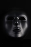 Anonymous black mask protruding from pitch black background. Royalty Free Stock Image