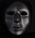 Anonymous black mask protruding from pitch black background. Stock Photos