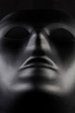 Anonymous black mask protruding from pitch black background - he Royalty Free Stock Photo