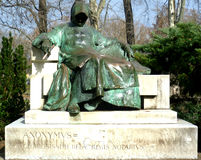 Anonymous. Bronze statue of a seated Anonymus in monk's habit and a cowl obscuring his face Stock Photos