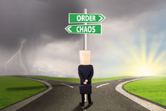Anonymous businessman facing options. Anonymous businessman standing on the road looking at signpost of order and chaos Stock Images