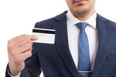 Anonymous businessman holding empty credit card. Anonymous businessman holding empty white credit card as safe payment concept isolated on white background Royalty Free Stock Photography