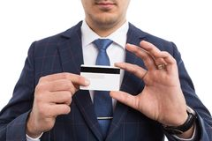 Anonymous businessman holding empty credit card. Anonymous businessman or salesman holding empty credit card as secure online payment concept isolated on white Stock Image