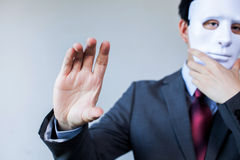 Anonymous businessman in mask hiding himself having holding something gesture - with copyspace Stock Image