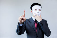 Anonymous businessman in mask hiding himself touching on virtual screen. With copyspace royalty free stock photo