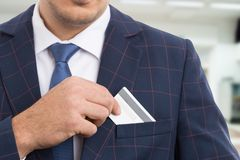 Anonymous businessman placing empty credit card. Anonymous businessman placing empty white credit card in suit jacket pocket as noncash secure payment concept Royalty Free Stock Images