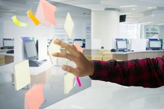 Anonymous businessman putting sticky notes in office. Closeup of anonymous businessman putting blank sticky notes on the transparent screen. Shot in the office Royalty Free Stock Photography