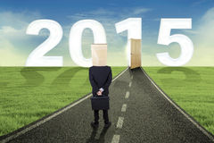 Anonymous businessman on the road. Businessman with cardboard head standing on the road to future 2015 Stock Images