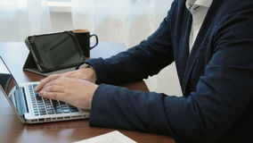 Anonymous businessman working at his desk in his office in front of the laptop computer typing with a tablet the. In this stock footage you can see young stock video footage