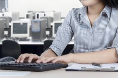 Anonymous businesswoman with computer. Picture of anonymous businesswoman working with a computer and clipboard on the desk Royalty Free Stock Photo