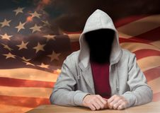 Anonymous Criminal in hood in front of American flag Royalty Free Stock Photos