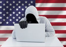Anonymous Criminal in hood with laptop in front of American flag Royalty Free Stock Photos