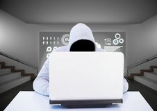 Anonymous Criminal in hood on laptop in front of interface Royalty Free Stock Photo